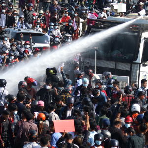 Vattenkanon monterad på en lastbil sprutar vatten på en samling demonstranter.