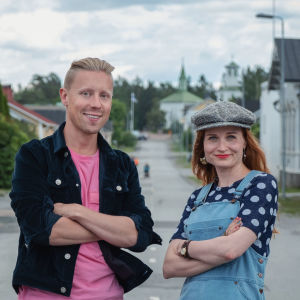 Egenland-ohjelman juontajat Nicke Aldén ja Hannamari Hoikkala seisovat keskellä katua Porin Reposaaressa, sivuilla näkyy puutaloja.