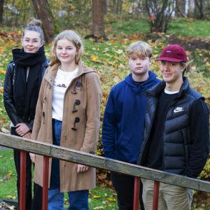 Fem ungdomar står på rad utomhus, de tittar in i kameran.