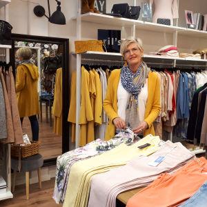 En kvinna står inne i en klädaffär omringad av kläder.
