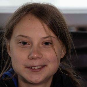 En närbild på en leende Greta Thunberg.