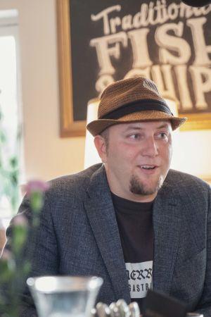 Mies hattu päässä, pikkutakki päällä, ravintolapöydän ääressä