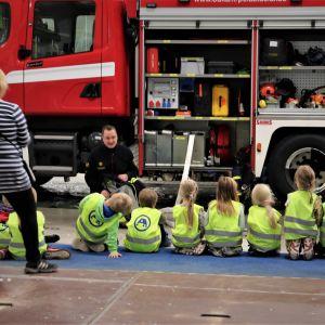 Lapset kuuntelemassa paloauton esittelyä.