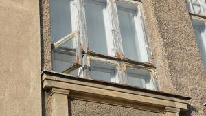 Ett öppet fönster i en husfasad av sten.