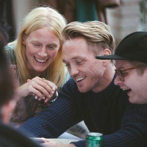 Ett gäng trettioplussare sitter samlade vid ett bord och skrattar tillsammans.