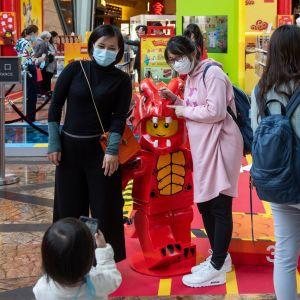 Två kvinnor med munskydd poserar för ett litet barn som tar bild. Kvinnorna står kring en röd legofigur.