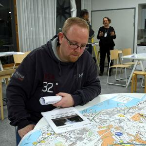 En man sitter vid ett runt bord och studerar en karta.