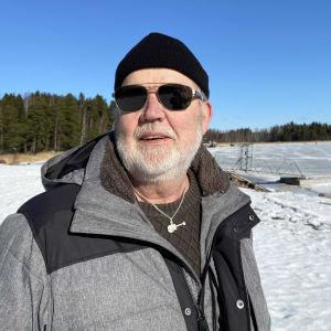Uffe Johansson står vid Kräkelsundet på vintern iklädd solglasögon.