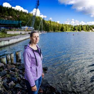 En kvinna i lila jacka står i en småbåtshamn.