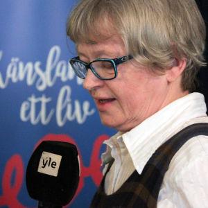 Kvinna håller i en mikrofon.