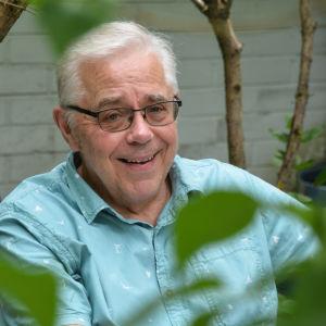 Egil Green sitter vid ett trädgårdsbord. Han ler och tittar in i kameran.