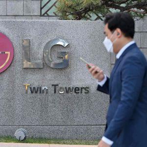 En man med munskydd och en telefon i handen går förbi en stor LG logga.