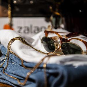Kuvassa on asetelma, jossa on vaatteita, asusteita ja lasituotteita Helsingissä marraskuussa 2020.