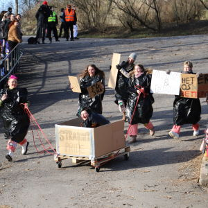 En grupp människor med rosa halare och skyltar påväg ner för backen.