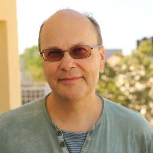 En medelålders man med solglasögon och grön t-skjorta.