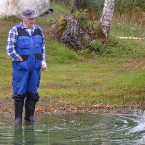 En äldre man i blå arbetsställ står med gummistövlar på sig en liten bit ut i vattnet.