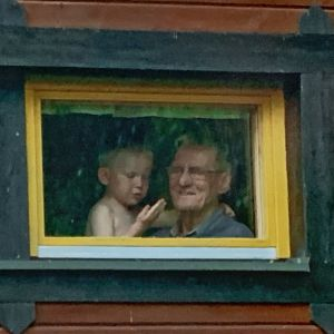 Anna-Elina Lyytikäisen Kyösti-poika on mökin ikkunasta ulos kohti kuvaajaa katsovan ukkinsa sylissä.