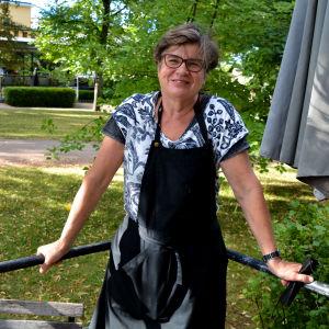 En kvinna som står och håller i ett räcke framför en park.