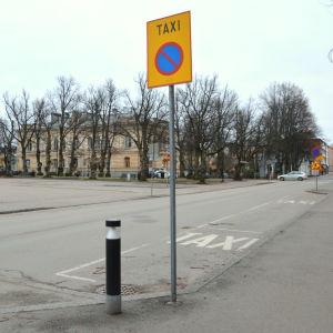 En taxistolpe vid sidan av en gata.