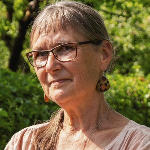 Äldre kvinna med långt hår på svans, pannlugg, glasögon, stora örhängen och ljus linneskjorta står med armarna i kors på en trädgårdsgång.