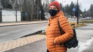 En kvinna i orange jacka och svart munskydd står invid en gata.