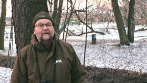 Miljöinspektör Raimo Pakarinen står med träd och Tölöviken i bakgrunden.
