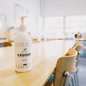 Käsidesi pullo kouluruokalassa.