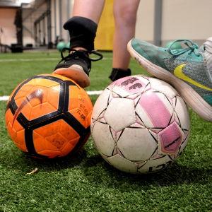 Fotbollar på konstgräs.