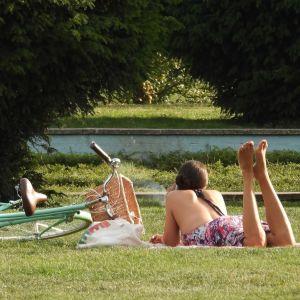 En kvinna ligger på mage på en filt i Battersea Park i London. Bredvid henne ligger en cykel.