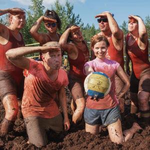 Grupp med män och kvinnor står och poserar på rad iklädda röda baddräkter, framför dem en man och en kvinna i pinka t-shorts, kvinnan håller i en volleyboll. Samtliga täckta med brun sörja.