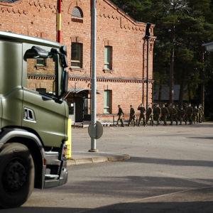 En lång rad med beväringar med munskydd går in i en tegelbyggnad. I förgrunden syns en lastbil som väntar på att köra in på garnisonsområdet.