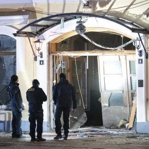 Poliisit tutkivat räjähdyksessa pahasti vaurioitunutta yökerhon sisäänkäyntiä.