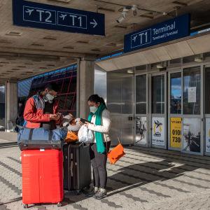 Helsinki-Vantaan lentoasemalla, Terminaali 1 edustalla, kaksi matkustajaa kasvosuojukset päällä.
