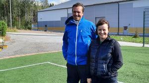 En man och en kvinna står vid sidan av en fotbollslan. De tittar in i kameran och ler.