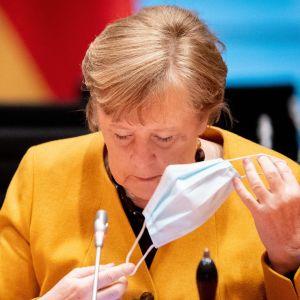 Angela Merkel, klädd i gult, tar av sig sitt munskydd framför en mikrofon.