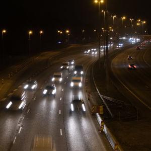 Biltrafik på en motorväg en mörk morgon.