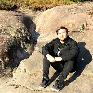 Henrik Nyholm sitter till höger om en fåra i berget.