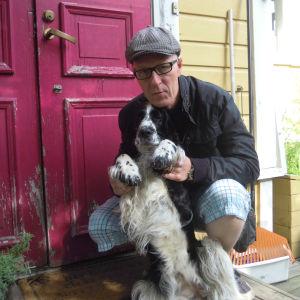 Tom Ridberg poserar i keps med en svarvit hund.