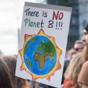"""En skylt med texten """"there is no planet b"""" (på svenska """"det finns ingen planet b"""" och en bild på ett jordklot som brinner. Demonstranter i bakgrunden."""