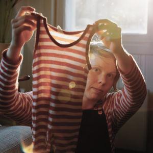 Minttu Turunlahti esittelee punaraidallista  vauvan bodya, jota Jenni on käyttänyt pienenä.