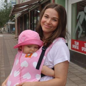 Sole Garghentino-Nygård med sin ettåriga dotter Lila i en bärväska på magen.
