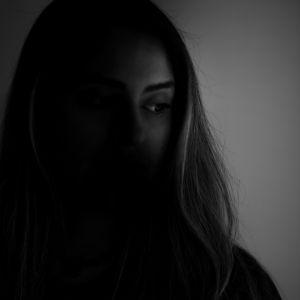 En svartvit bild på en rädd kvinna med långt hår vid ett fönster.