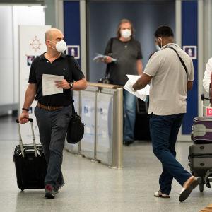 Matkustajia kävelee matkatavaroiden kanssa maskit kasvojensa edessään Helsinki-Vantaan lentoasemalla 7. elokuuta 2020.
