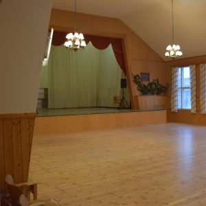 En tom sal med scen i ett föreningshus.