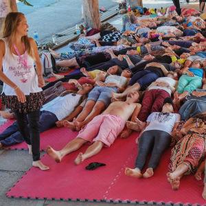 Ihmisiä makaa maassa, nauravat, vieressä seisoo naurava ohjaaja joogavaatteet päällä, ulkokatos, kesä, aurinko paistaa