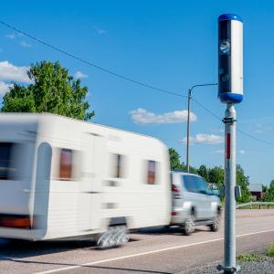 Hekilöauton vetämä matkailuvaunu ohittaa nopusvalvontakameran.