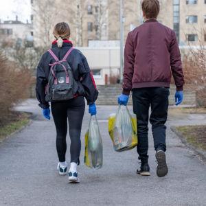 Helsinki-avun vapaaehtoiset Inga Strauss ja Miika Tulkki vievät ruokakasseja vanhuksille.