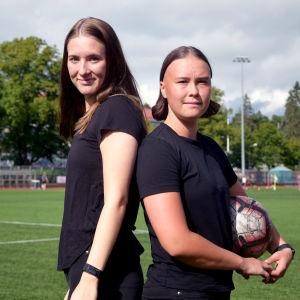 Felicia Gröning och Jill Illman står på en konstgräsplan och håller i en fotboll.