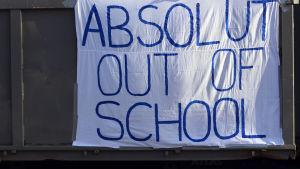 Ungdomar står på ett lastbilsflak. På sidan av flaket står det Absolut out of school.