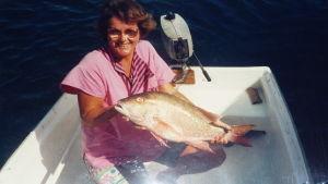 Bild på unga Anneli Sarekoski som fått fisk. Hon sitter i en mindre glasfiberbåt